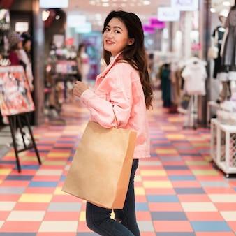 Вид спереди милой японской девушки за покупками