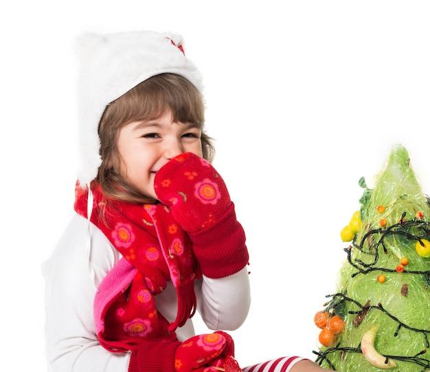 크리스마스 트리를 장식하는 귀여운 즐거운 아이의 전면 모습.