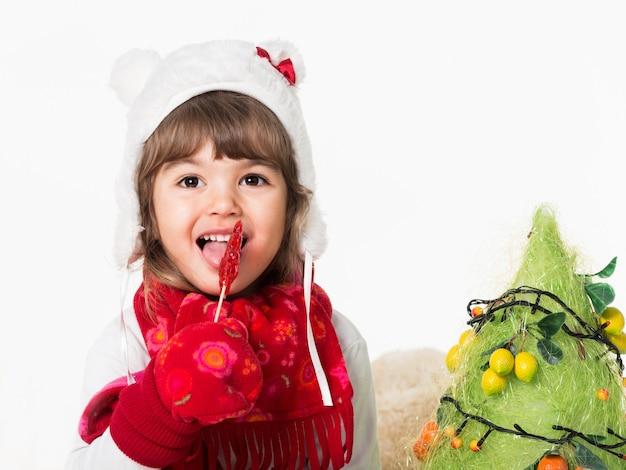 Вид спереди милый радостный ребенок, облизывающий красный вкусный леденец на палочке.