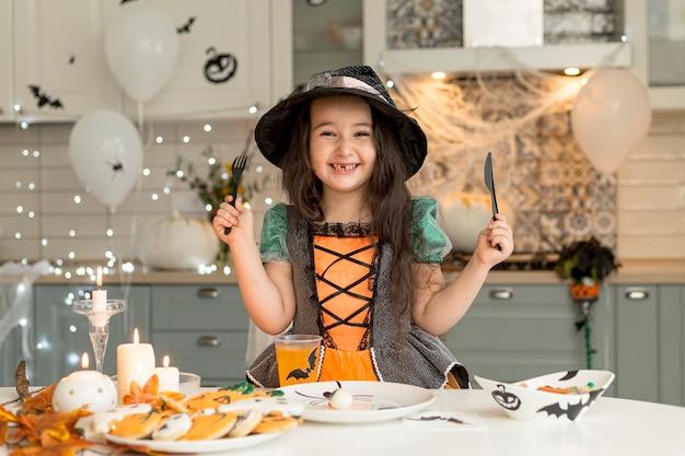 Вид спереди милой маленькой девочки в костюме ведьмы