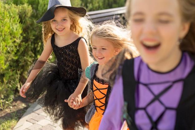 Вид спереди милых маленьких девочек в костюмах на хэллоуин