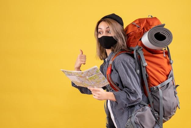 後ろを指す地図を保持している黒いマスクとバックパックを持つかわいい旅行者の女の子の正面図