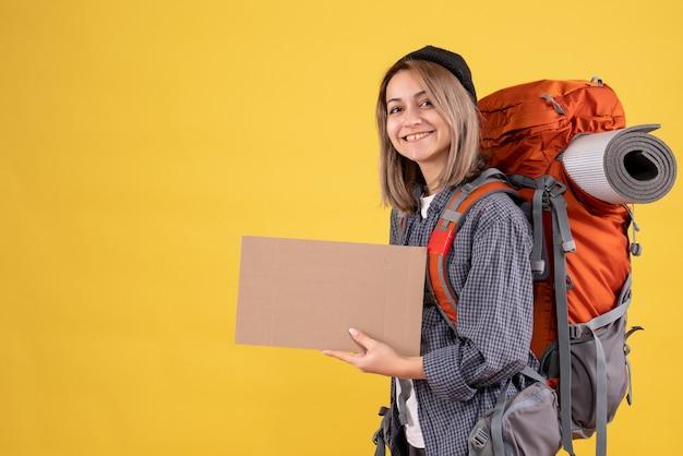 段ボールを保持している赤いバックパックとかわいい旅行者の女の子の正面図