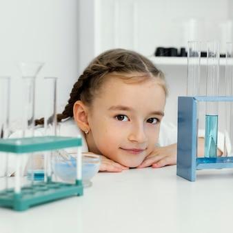 Вид спереди симпатичной молодой девушки-ученого с пробирками