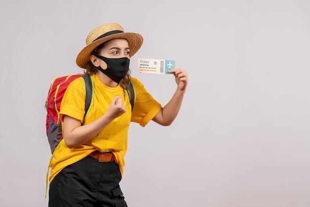 灰色の孤立した壁に旅行チケットを保持しているバックパックとかわいい若い旅行者の正面図