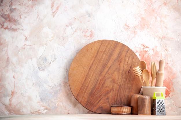 カラフルな表面にまな板の木のスプーンおろし金の正面図