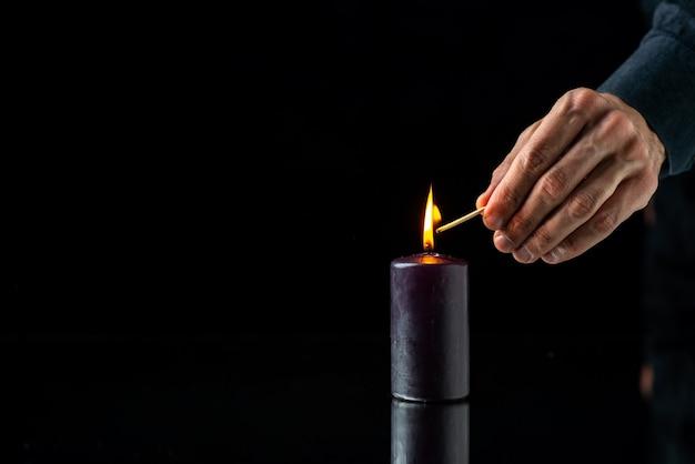 暗い表面で男性によって明るくなる暗いキャンドルの正面図