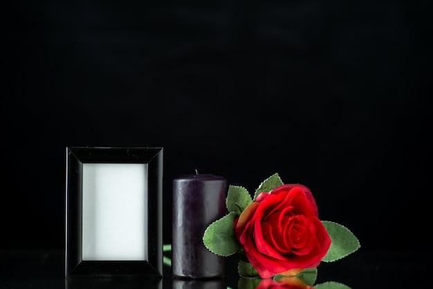 Вид спереди темной свечи с красной розой и рамкой для рисунка на темной поверхности
