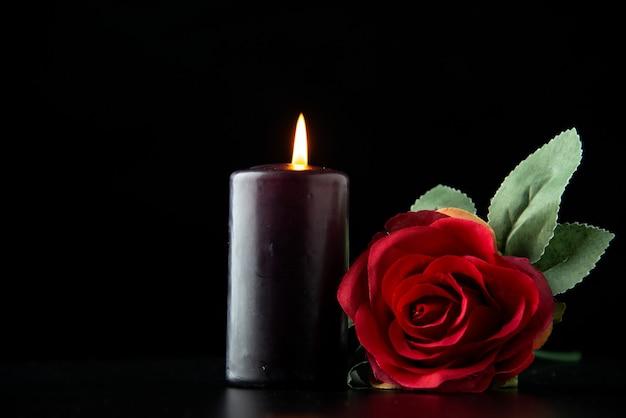 Вид спереди темной свечи с красной розой на темной поверхности
