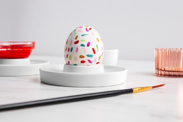 Вид спереди украшенного пасхального яйца на тарелке с краской и кистью