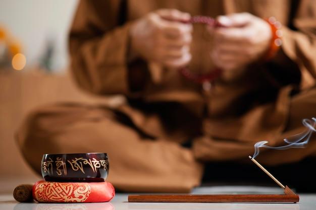 Расфокусированный мужчина, медитирующий с бусами рядом с поющей чашей, вид спереди