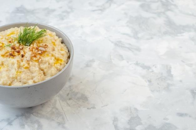 여유 공간이 있는 얼음 배경의 오른쪽 그릇에 녹색과 함께 제공되는 귀리와 함께 맛있는 아침 식사의 전면 전망