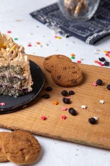 Вид спереди вкусного кусочка торта внутри темной тарелки со свечами печеньем и маленькими знаками зодиака на светлом столе