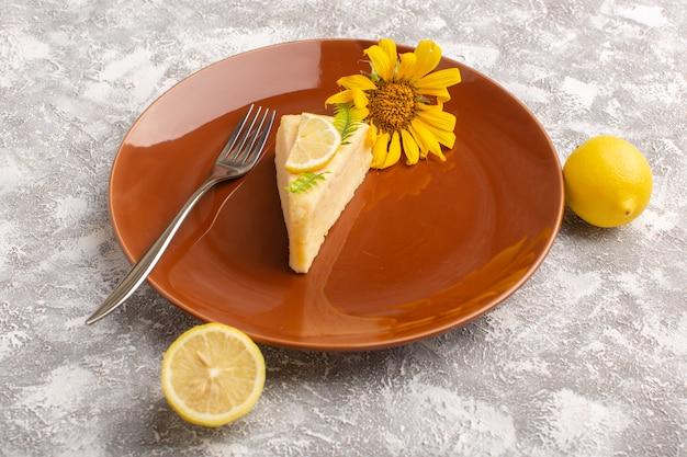 Вид спереди вкусный торт ломтик с лимоном внутри коричневой пластины на светлой поверхности