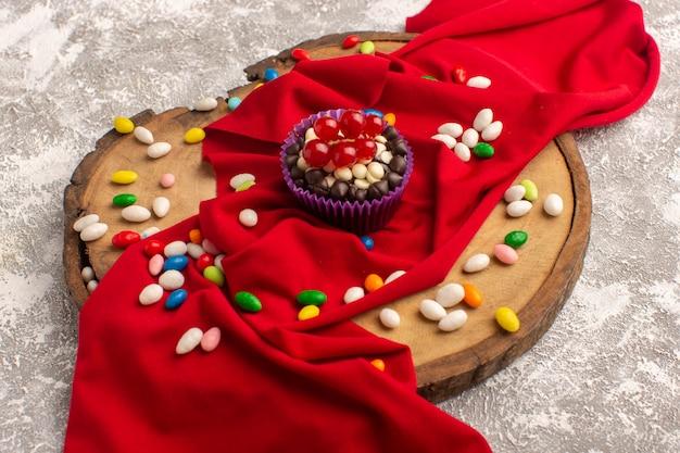 Вид спереди вкусного шоколадного пирожного с разноцветными конфетами на светлой поверхности