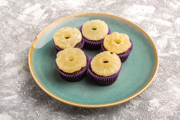 Вид спереди вкусные шоколадные пирожные с кольцами ананаса внутри зеленой тарелке на светлой поверхности