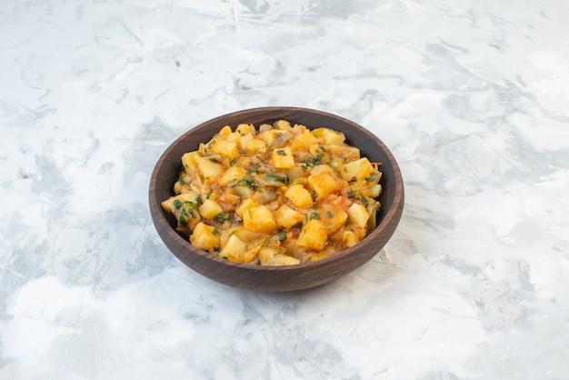 여유 공간이 있는 얼음 배경에 있는 갈색 그릇에 녹색 감자 야채와 함께 맛있는 저녁 식사의 전면 보기