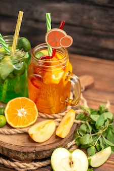 갈색 배경에 나무 쟁반에 맛있는 신선한 주스와 과일의 전면보기