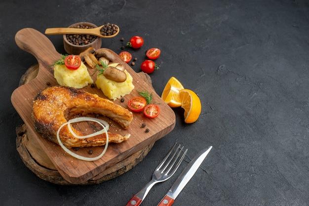 おいしい揚げ魚とキノコの正面図 まな板のカトラリー セット コショウの上のトマト グリーン 黒い表面