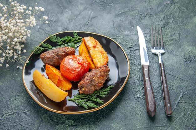Вид спереди вкусных мясных котлет, запеченных с картофелем и помидорами на черной тарелке, набор столовых приборов, белые цветы на зеленом черном фоне смешанного цвета