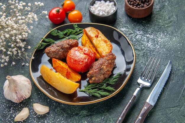 검은 접시에 감자와 토마토로 구운 맛있는 고기 커틀릿의 전면 전망은 녹색 검정 혼합 색상 배경에 흰색 꽃 향신료 마늘을 설정합니다.