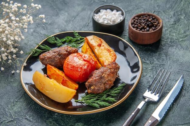 검은 접시에 감자와 토마토로 구운 맛있는 고기 커틀릿의 전면 전망은 녹색 검정 혼합 색상 배경에 흰색 꽃 향신료를 설정합니다