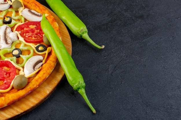 赤いトマト、ベルペッパー、オリーブのキノコのおいしいピザの正面図