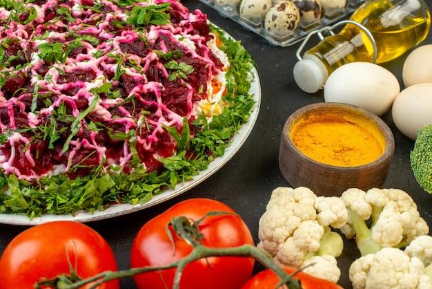 검은 배경에 녹색 계란 신선한 야채 노란색 생강으로 장식된 맛있는 샐러드의 전면 보기