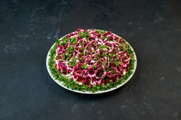 여유 공간이 있는 검정색 배경에 흰색 접시에 녹색으로 장식된 맛있는 샐러드의 전면 보기