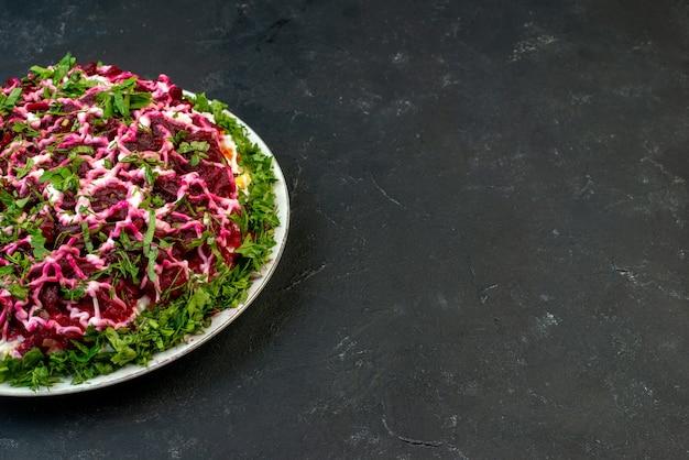 여유 공간이 있는 검정색 배경의 오른쪽에 있는 흰색 접시에 녹색으로 장식된 맛있는 샐러드의 전면 보기