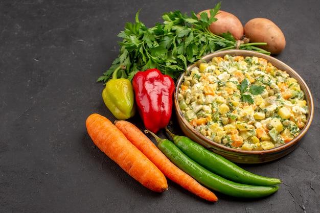 暗い表面に新鮮な野菜とおいしいサラダの正面図