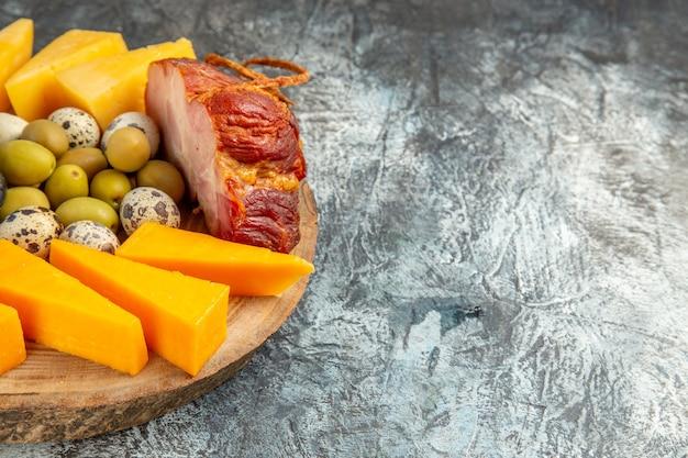 Вид спереди вкусной закуски, включая фрукты и продукты, на коричневом подносе на фоне льда