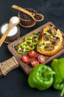 검은 배경에 버섯 신선한 야채와 향신료를 곁들인 맛있는 간식의 전면