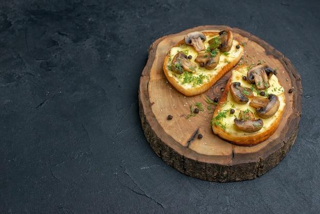 여유 공간이 있는 검정색 배경의 왼쪽에 있는 나무 판자에 버섯이 있는 맛있는 간식의 전면 보기