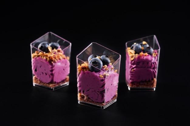 Вид спереди вкусного сладкого десерта в трех маленьких бокалах подряд, изолированных на черном фоне. вкусное парфе с гранолой, черникой сверху и ярко-фиолетовыми взбитыми сливками.