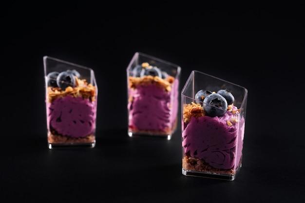 Вид спереди восхитительного сладкого десерта мюсли в трех маленьких стаканах в ряд. вкусное парфе с мюсли, черникой сверху и ярко-фиолетовыми взбитыми сливками, изолированными на черном фоне.