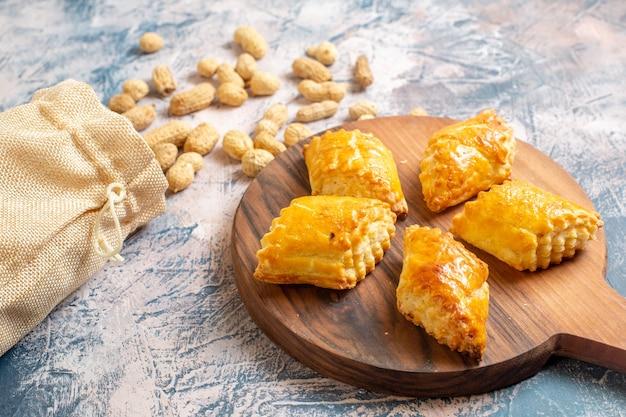 青い表面にピーナッツが付いているおいしい甘いペストリーの正面図