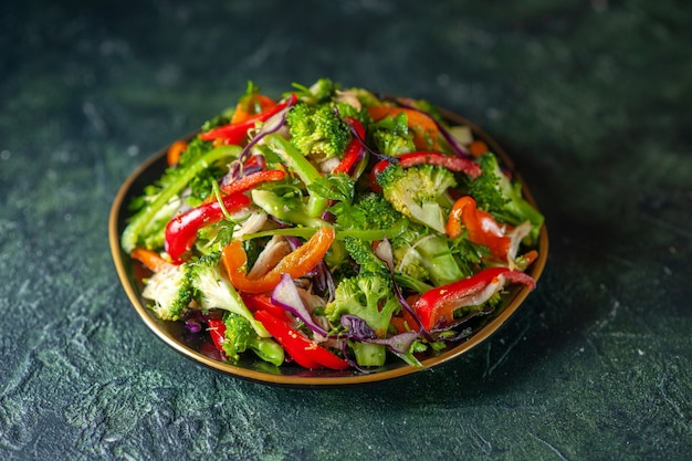 Вид спереди вкусного овощного салата с различными ингредиентами на темном фоне