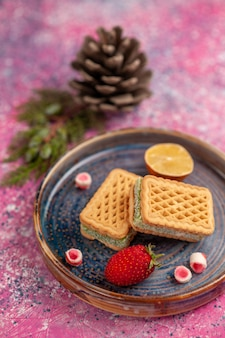 ピンクの表面においしいワッフルサンドイッチの正面図