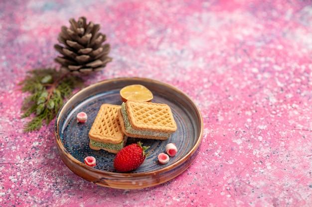 ピンクの机の上のおいしいワッフルとイチゴ1個の正面図
