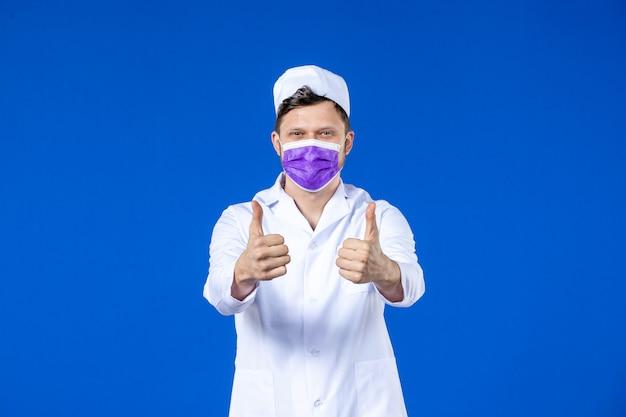 파란색 벽에 의료 양복과 보라색 마스크에 기쁘게 남성 의사의 전면보기