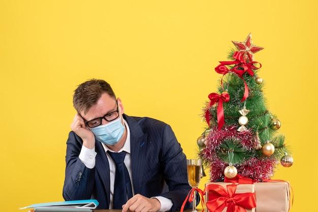 クリスマスツリーの近くのテーブルに座って、黄色で提示する落ち込んでいるビジネスマンの正面図