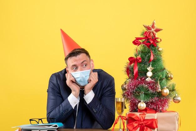 クリスマスツリーの近くのテーブルに座っているパーティーキャップと黄色のプレゼントと落ち込んでいるビジネスマンの正面図