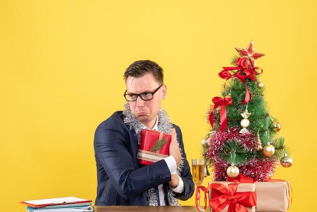 クリスマスツリーの近くのテーブルに座って彼の贈り物を隠し、黄色で提示する落ち込んでいる男の正面図
