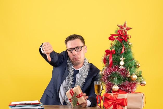クリスマスツリーの近くのテーブルに座って、黄色で提示する親指ダウンサインを作る落ち込んでいる男の正面図