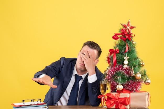 クリスマスツリーの近くの手と黄色の贈り物で彼の目を覆っているテーブルに座っている落ち込んでいる男の正面図