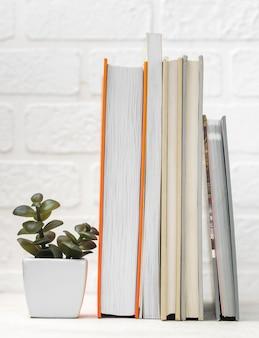 쌓인 책과 식물이있는 책상의 전면보기
