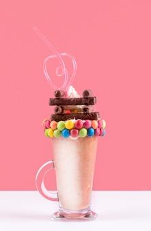 Вид спереди десертного стекла с соломой и разноцветными конфетами