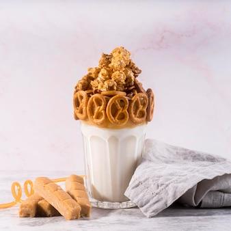 Вид спереди десерт в стакане с кренделями и тканью