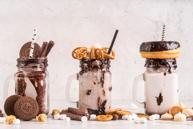 Вид спереди десертов в банках с печеньем и пончиками